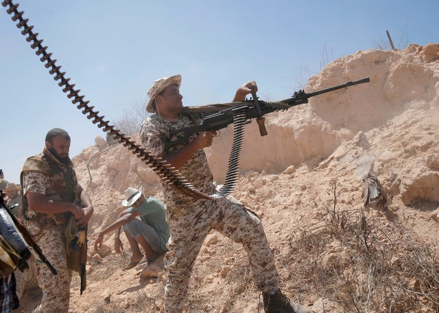 A fighter of Libyan forces allied with the U.N.-backed government fires a weapon during a battle with IS fighters in Sirte, Libya, July 21, 2016. REUTERS/Goran Tomasevic