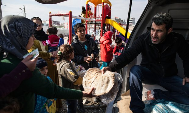 A woman receives a bread ration in a refugee camp for Syrians near the town of Akçakale and the Syrian border, Turkey. More than 1,000 refugees in Turkey have been blocked from resettling in the US due to their university qualifications. Photograph: Holly Pickett for the Guardian