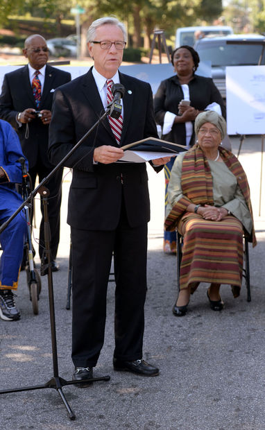 Mayor Allen Joines reads a proclaimation giving the honorary name of President Sirleaf Lane to Liberia Street in the Happy Hill neighborhood in honor of President Ellen Johnson Sirleaf (seated).