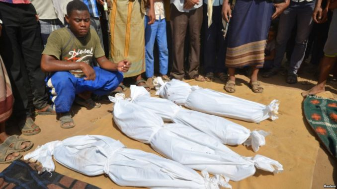 VOA FILE - A man sits as others stand near the wrapped up bodies of children, one day after they were killed in a Saudi-led airstrike on their house in Bajil district of the Red Sea province of Houdieda, Yemen, Oct. 8, 2016.