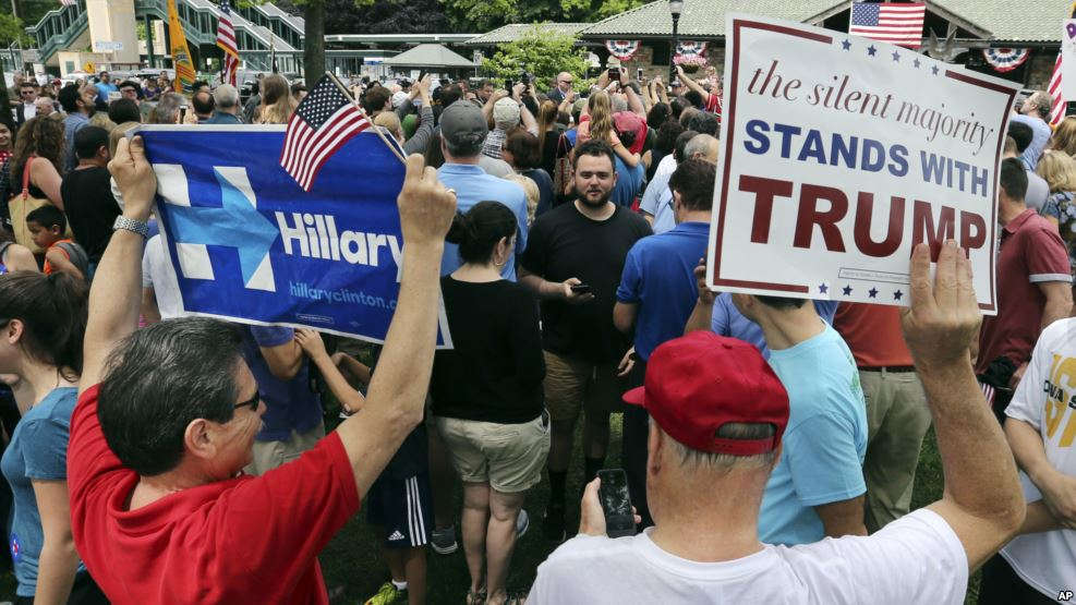 A supporter of Democratic presidential candidate Hillary Clinton and a Republican presidential candidate Donald Trump supporter hold signs as they attend a Memorial Day parade, May 30, 2016, in Chappaqua, N.Y. (Credit/VOA)