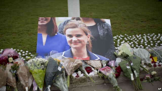 An image and floral tributes for Jo Cox, the 41-year-old British Member of Parliament shot to death yesterday in northern England, lie placed on Parliament Square outside the House of Parliament in London, June 17, 2016.