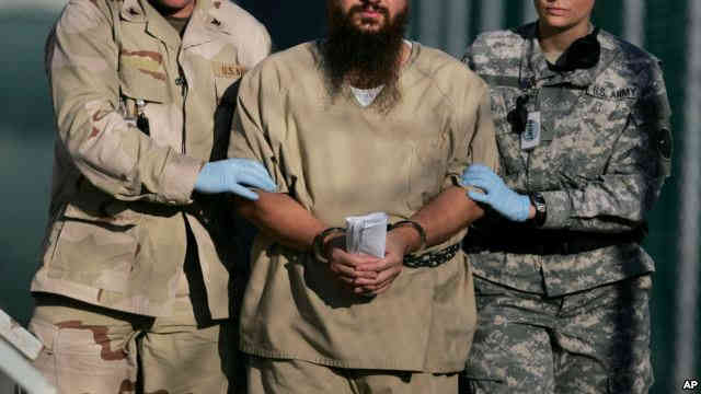 FILE - A shackled detainee is being escorted away from an Administrative Review Board hearing, at Camp Delta detention center at the Guantanamo Bay U.S. Naval Base in Cuba, Dec. 6, 2006./VOA