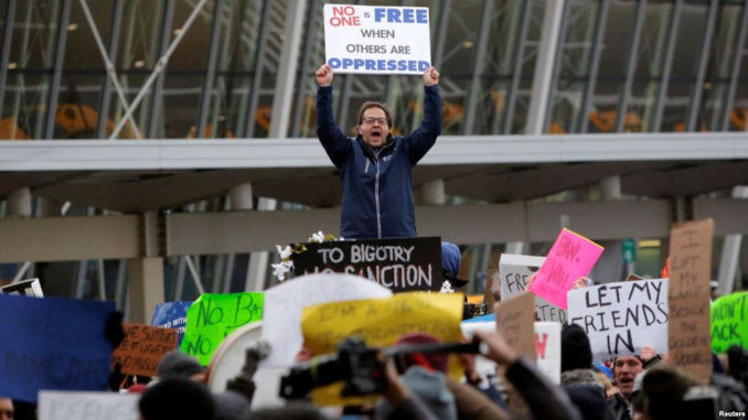 A man yells during a protest against Donald Trump's travel ban outside Terminal 4 at John F. Kennedy International Airport in Queens, New York, Jan. 28, 2017 (CREDIT VOA).