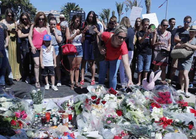 A woman puts flowers near the scene where a truck mowed through revelers in Nice, southern France, July 15, 2016.