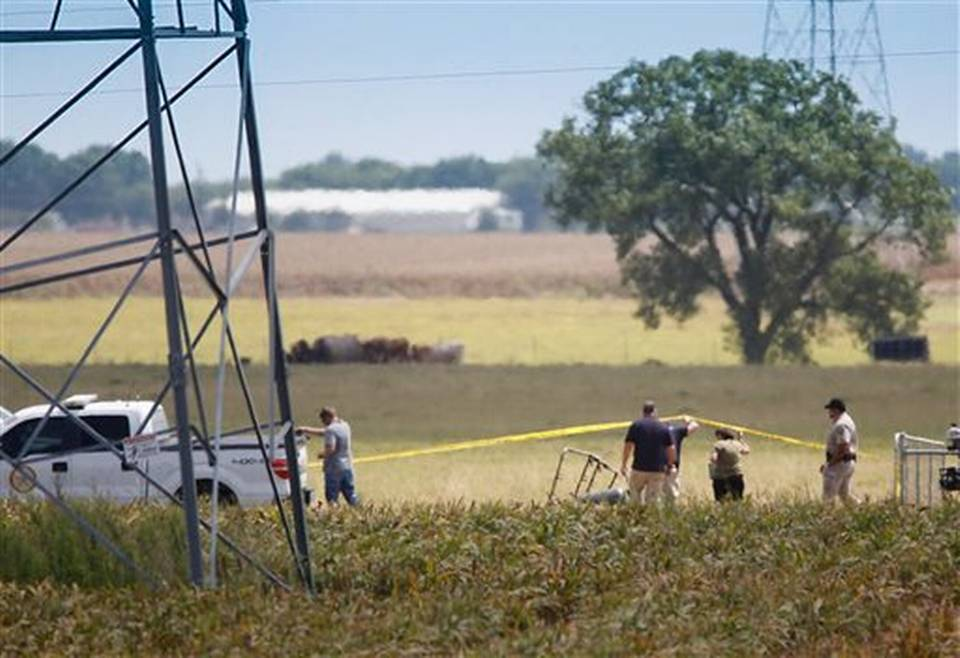 """Investigators surround the scene in a field near Lockhart, Texas where a hot air balloon carrying at least 16 people collided with power lines Saturday, July 30, 2016, causing what authorities described as a """"significant loss of life."""" Austin American-Statesman via AP Ralph Barrera"""