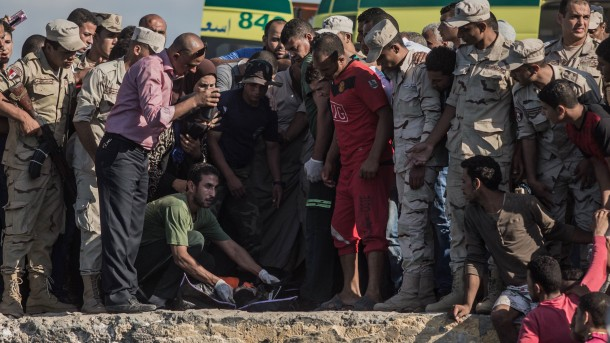 Egyptian coast guard personnel, rescue workers and family members look to identify a body that was brought ashore in Rosetta, Egypt