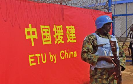 A UN Soldier stands guard outside opening of an Ebola virus clinic sponsored by China, in Monrovia, Liberia, November, 2014. Abbas Dulleh / Press Association.
