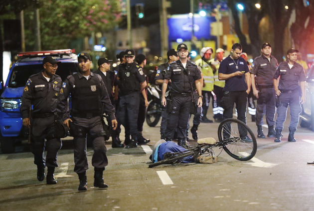 Police stand near the body of a man who was shot and killed.