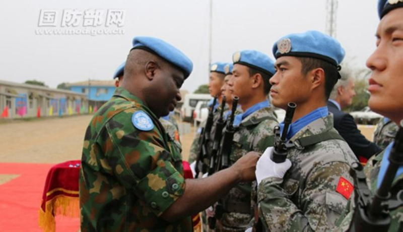 Chinese peacekeeper assigned to the 19th Chinese peacekeeping detachment to Liberia is presented a UN Peace Medal of Honor at their barracks in Monrovia,  all the 124 members of the 19th Chinese peacekeeping force to Liberia were awarded the UN peace medals for their excellent performance in Liberia. (mod.gov.cn/ Zou Cungang, Yu Hang)