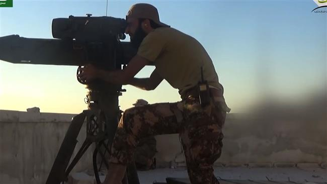 This screen grab on July 12, 2016 shows a militant firing a US-made TOW missile toward Syrian soldiers positioned on Aleppo's city hall's rooftop, which is located in a government-held neighborhood. (Photo by AFP)