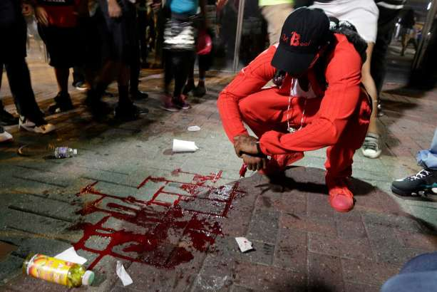 A man squats near a pool of blood after a man was injured during a protest