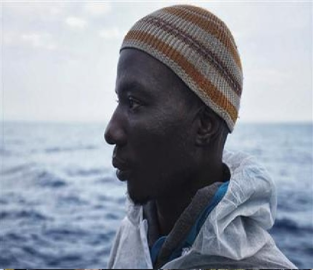 In this photo taken on Saturday June 25, 2016, Laye Donzo from Liberia poses for a photograph on the Aquarius vessel after being rescued on the Mediterranean Sea. The ordeal of Laye Donzo is a cautionary story for the tens of thousands of Africans each year who take the migrant road to Libya, seeing it as the gateway to life and prosperity in Europe. Instead, for many the war-torn country has meant only prolonged abuse. (AP Photo/Bram Janssen)