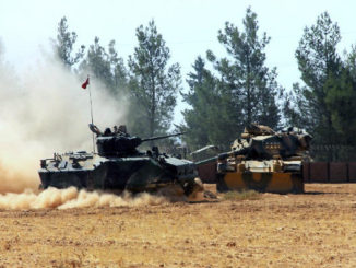 A Turkish army tank and an armoured vehicle are stationed near the border with Syria, in Karkamis, Turkey