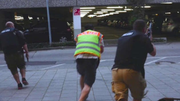 A screen grab taken from video footage shows plain clothes police officers running towards car park of the Olympia shopping mall during shooting rampage in Munich, Germany July 22, 2016.  dedinac/Marc Mueller/ handout via REUTERS  NO ARCHIVES. FOR EDITORIAL USE ONLY. NOT FOR SALE FOR MARKETING OR ADVERTISING CAMPAIGNS. THIS IMAGE HAS BEEN SUPPLIED BY A THIRD PARTY. IT IS DISTRIBUTED, EXACTLY AS RECEIVED BY REUTERS, AS A SERVICE TO CLIENTS.  TPX IMAGES OF THE DAY
