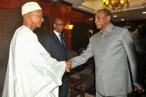 AFP | Guinea's President Alpha Conde (R) shakes hands with opposition leader Cellou Dalein Diallo during their meeting at the presidential palace in Conakry