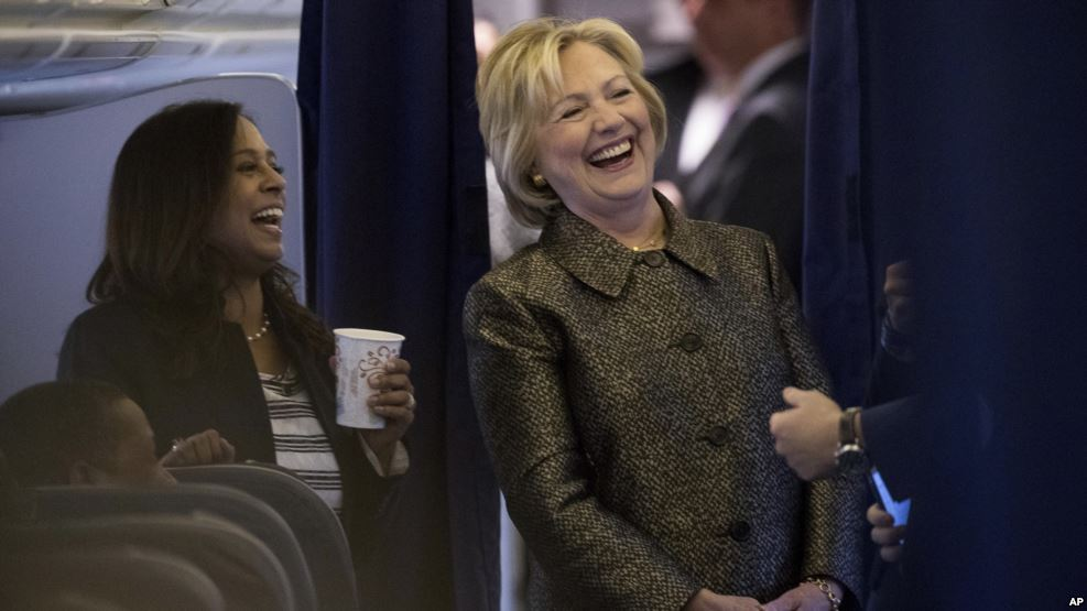 Democratic presidential candidate Hillary Clinton laughs with Senior Policy Advisor Maya Harris, left, and other staff members aboard her campaign plane in White Plains, N.Y., Oct. 2, 2016.