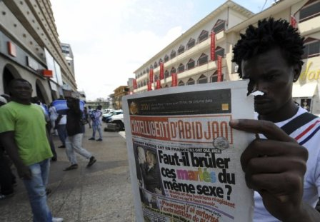 A man reads the a daily newspaper showing on its front page a picture of a gay couple kissing and the headline: 'Should these same-sex married couple be burnt?' in May 2013 in the commercial capital AbidjanSia Kambou /AFP/Getty Images