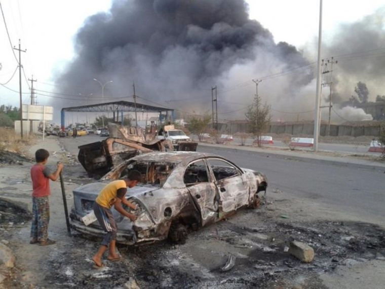 Children stand next to a burnt vehicle during clashes between Iraqi security forces and ISIS fighters in Mosul, Iraq