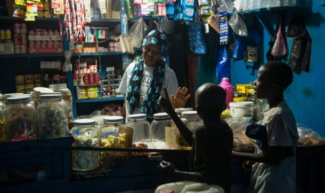 A shop in Sayon Town, where children can buy snacks. A single light bulb there is powered by a generator. Credit Jim Tuttle for The New York Times