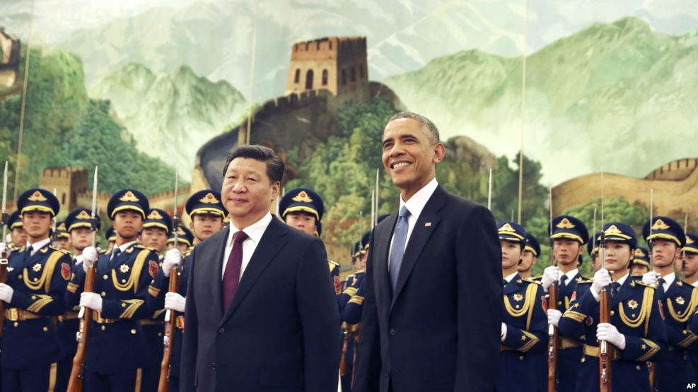 VOA FILE - U.S. President Barack Obama, right, smiles after a group of children waved flags and flowers to cheer him during a welcome ceremony with Chinese President Xi Jinping at the Great Hall of the People in Beijing, China, Nov. 12, 2014.
