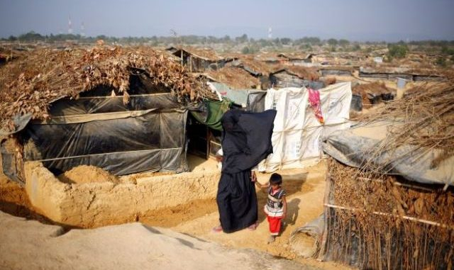 A Rohingya refugee woman with her child walks at Kutupalang makeshift refugee camp in Cox's Bazar, Bangladesh, Feb 12, 2017. - Reuters
