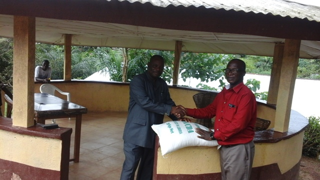 Superintendent Brown presenting a 25KG bag of rice from his farm to our staff as a gift for his tour in the county