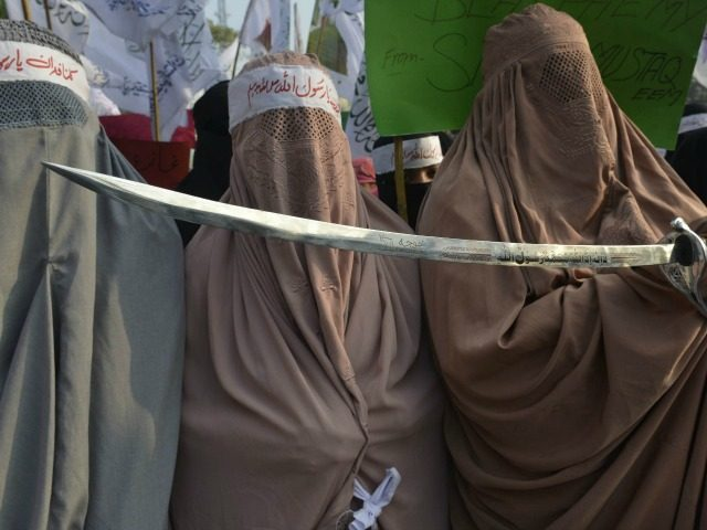 Pakistan women demonstrators wear burqas and hold a sword in protest against the printing of satirical sketches of the Prophet Muhammad by French magazine Charlie Hebdo, in Lahore on January 20, 2015. Pakistan's parliament on January 15 condemned French satirical magazine Charlie Hebdo for printing a 'blasphemous' cartoon of the Prophet Mohammed as religious groups held rallies throughout the country, including one during which the Tricolour was burnt. AFP PHOTO / Arif ALI (Photo credit should read Arif Ali/AFP/Getty Images)