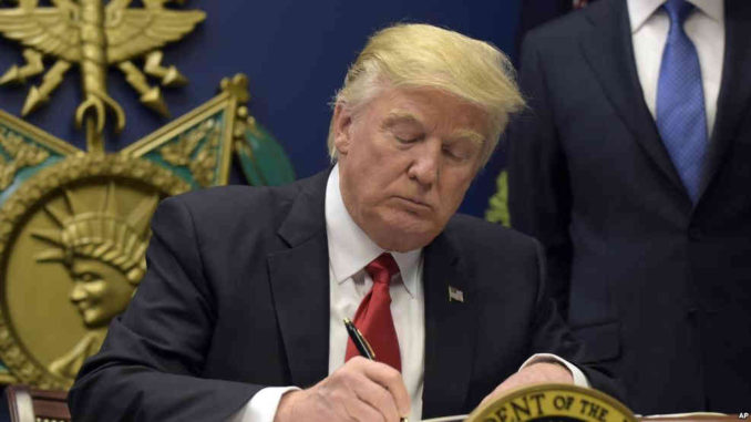 President Donald Trump signs an executive order on extreme vetting during an event at the Pentagon in Washington, Jan. 27, 2017. (VOA CREDIT)