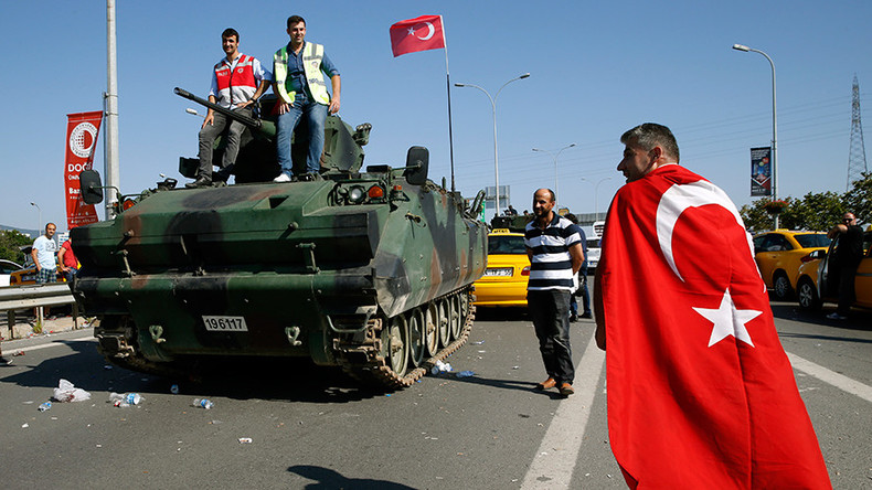 A man wrapped in a Turkish flag walks past a military vehicle in front of Sabiha Airport, in Istanbul, Turkey July 16, 2016 © Baz Ratner / Reuters
