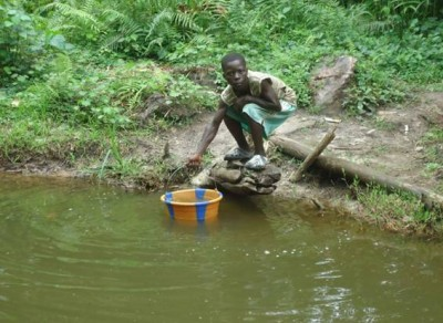 A kid demonstrating how residents of Gwekpozue Town used to fetch water