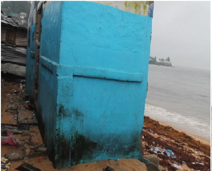 A house with a tiger worms toilet lying in ruins after sea erosion