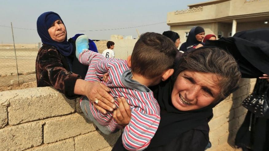 Women carry a boy over a wall as civilians flee their houses in the village of Tob Zawa, Iraq, about 9 kilometers (5.6 miles) from Mosul, Tuesday, Oct. 25, 2016, as Iraq's elite counterterrorism forces fight against Islamic State militants. (AP Photo/Khalid Mohammed)  (The Associated Press)