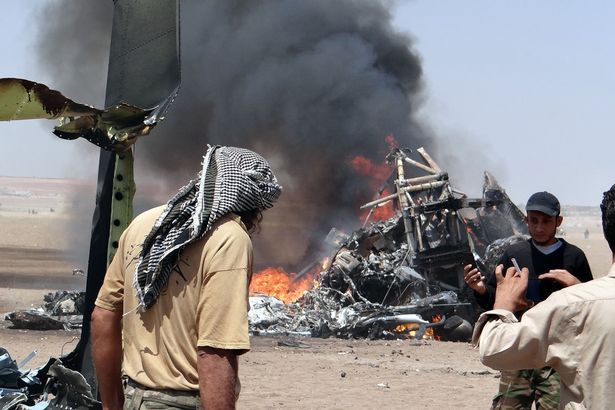 Syrians surround the wreckage of a downed Russian helicopter