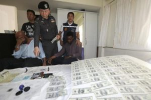 Thailand Immigration police chief Nathathorn Prousoontorn, centre, shows Liberian men David Neal, right, and Mathas Davies, left, who were arrested with fake US dollar notes in the lower Sukhumvit area, Bangkok