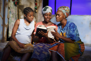 """This photo provided by The Public Theater shows, Pascale Armand, from left, Lupita Nyong'o, and Saycon Sengbloh in """"Eclipsed,"""" written by Danai Gurira, in New York. In an effort to shine a light on the hundreds of girls abducted from a school in Nigeria two years ago, all performances of the Broadway play """"Eclipsed"""" will be dedicated to the still-missing victims. Gurira said Friday, April 22, 2016, that each future performance of her play will be dedicated to a girl who has been abducted by the Boko Haram and will be named in her honor. (Joan Marcus/The Public Theater via AP)"""