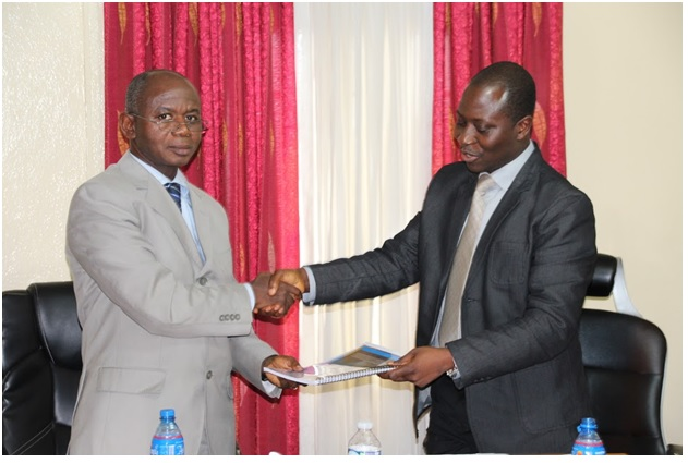 LEITI Head of Secretariat Konah D. Karmo (Right) presents the 8th EITI Report for Liberia to Mr. Stephen Dorbor, Deputy Minister for Planning, MLME.