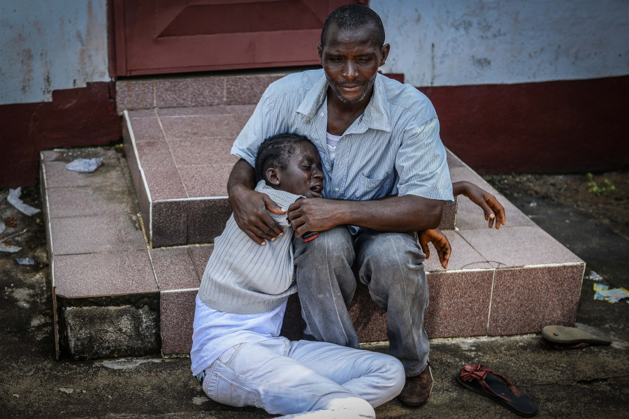 MONROVIA, LIBERIA - OCTOBER 10:  Relatives of Hanfen John who died due to the Ebola virus, mourn for him in Monrovia, Liberia on 10 October, 2014. (Photo by Mohammed Elshamy/Anadolu Agency/Getty Images)