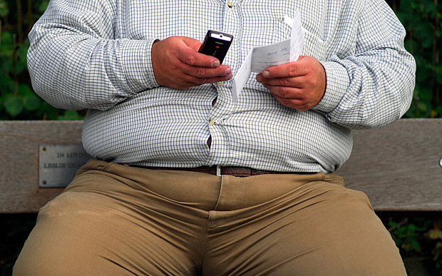 AGY01X Obese man sending a text message from mobile phone, Surbiton, UK.. Image shot 2007. Exact date unknown.