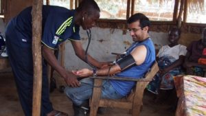 Dr. Raj Panjabi has his blood pressure checked by a Liberian community health worker