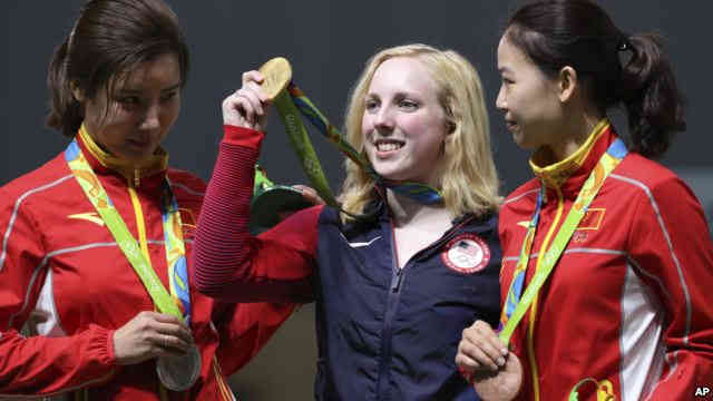 Virginia Thrasher, center, of the United States holds her gold medal for the Women's 10m Air Rifle competition during the award ceremony at the 2016 Summer Olympics in Rio de Janeiro, Brazil, Aug. 6, 2016./VOA News